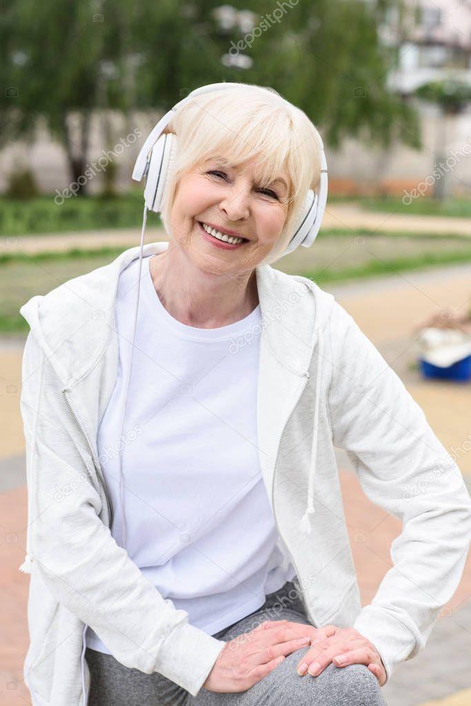smiling elderly woman listening music in headphones