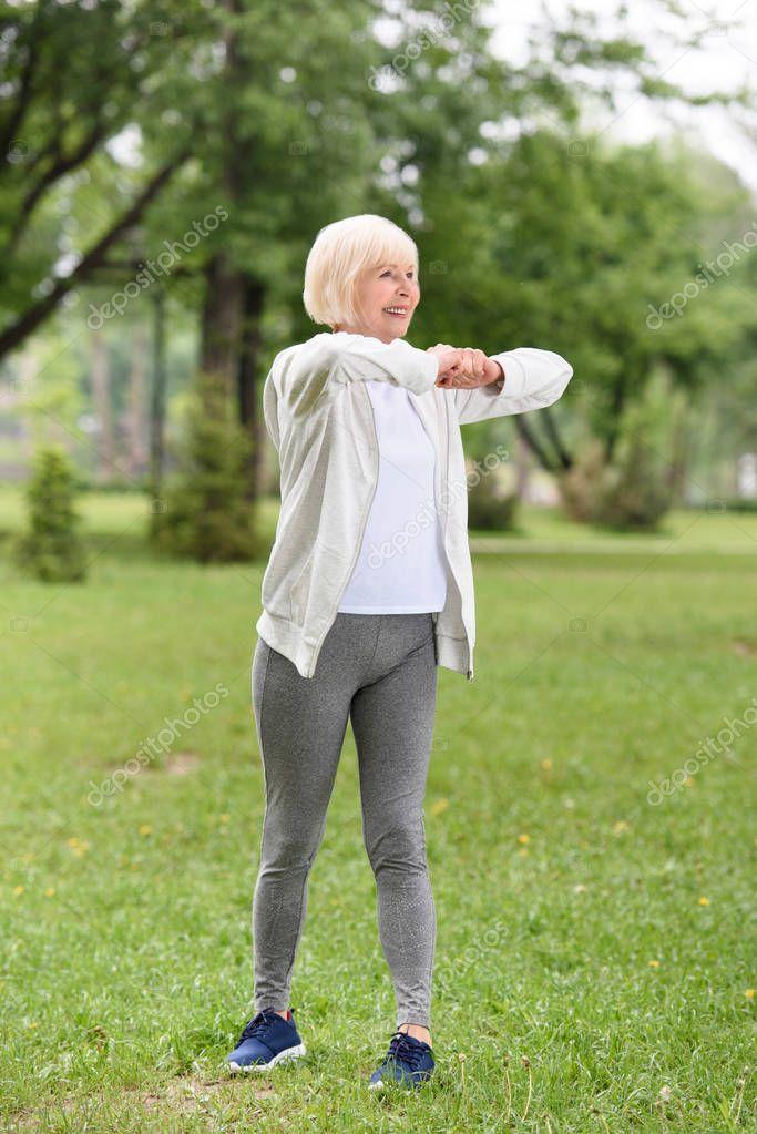 senior caucasian sportswoman exercising on green lawn in park