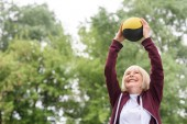 Seniorensportlerin trainiert mit Medizinball im Park