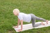 Fotografie Starší žena cvičí jóga podložku na trávníku