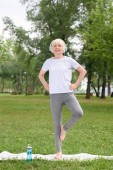 Fotografie senior female yogi in headphones practicing on yoga mat in park