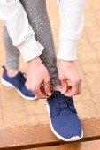 Ausgeschnittene Ansicht einer Sportlerin, die Schnürsenkel an Turnschuhen bindet