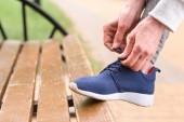 Fotografia vista parziale di legare i lacci delle scarpe scarpe da ginnastica sportiva