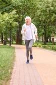 Lächelnde Seniorin läuft im Park