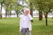 vedoucí sportovkyně s sportovní láhev poslech hudby se sluchátky v parku