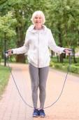 Seniorensportlerin trainiert mit Springseil im Park