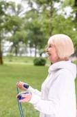 Fotografie glücklich senior Sportlerin training mit Springseil im park
