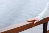 Fotografia vista parziale della mano femminile su ringhiere in legno