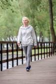 Seniorin in Sportkleidung läuft auf Holzweg in Park am Fluss