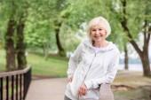 Fotografia donna maggiore sorridente in piedi vicino a ringhiere in Parco