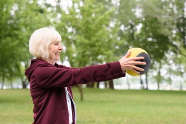 elderly woman exercising with medicine ball in park