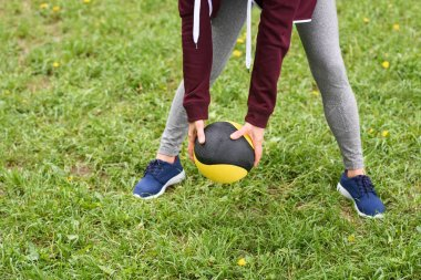 cropped view of woman training with medicine ball on green grass