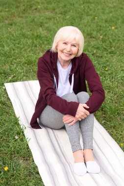 senior woman sitting on yoga mat on green lawn
