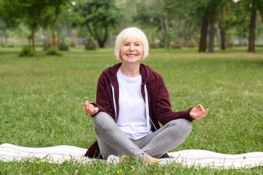 happy senior woman meditating with gyan mudra on yoga mat in park
