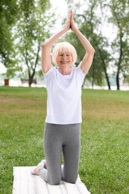 senior woman with namaste gesture practicing yoga on mat in park