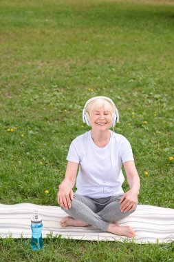 happy senior woman listening music with headphones while sitting on yoga mat in park