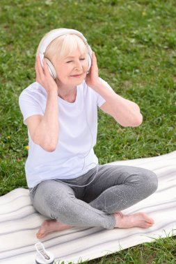 senior woman listening music with headphones while sitting on yoga mat