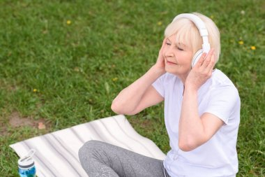 happy senior woman listening music with headphones while sitting on yoga mat on lawn