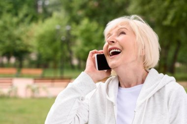laughing elderly woman talking on smartphone