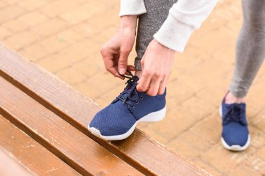cropped view of sportswoman tying shoelaces on blue sneakers