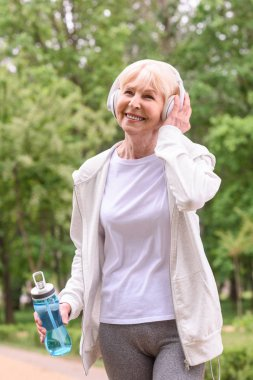 happy senior sportswoman with water listening music with headphones in park