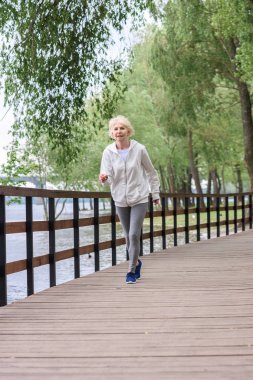 Senior sportswoman running on wooden path in park stock vector