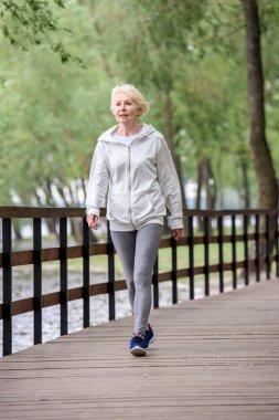 senior woman in sportswear walking on wooden path in park near river