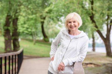smiling senior woman standing near railings in park