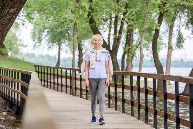 senior woman in sportswear walking on wooden path in park