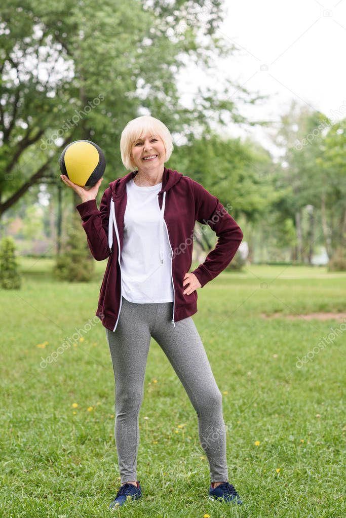 cheerful senior sportswoman posing with medicine ball in park