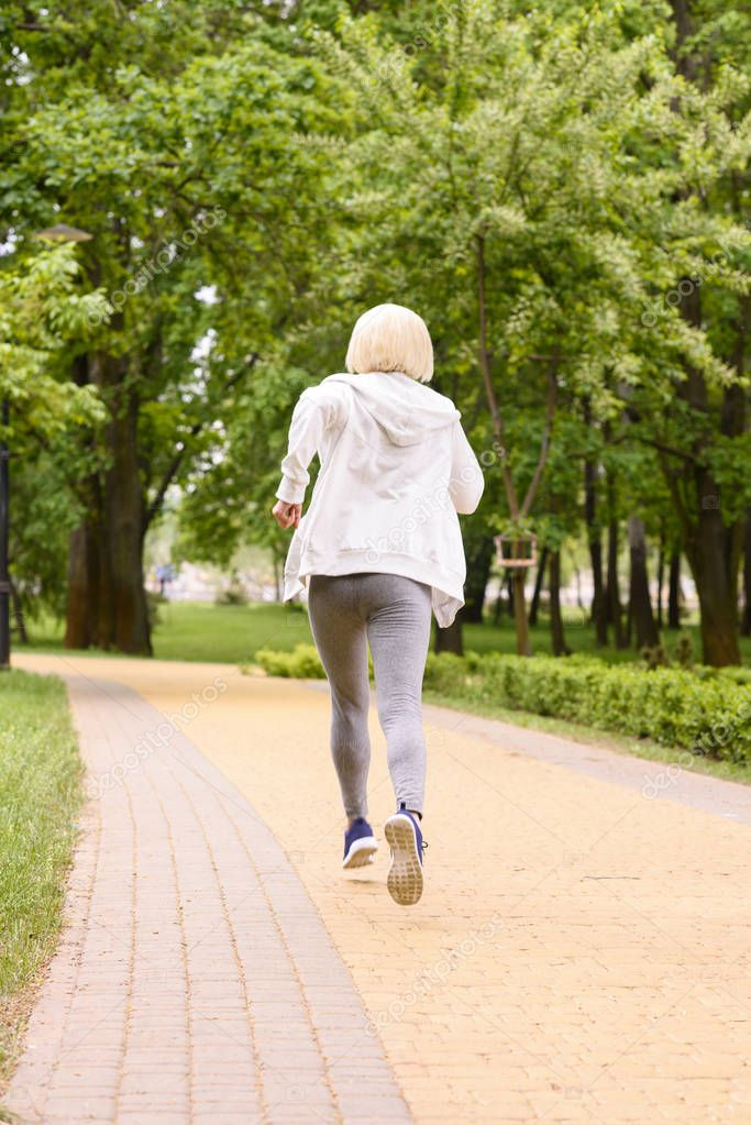 back view of sportive woman with grey hair jogging in park