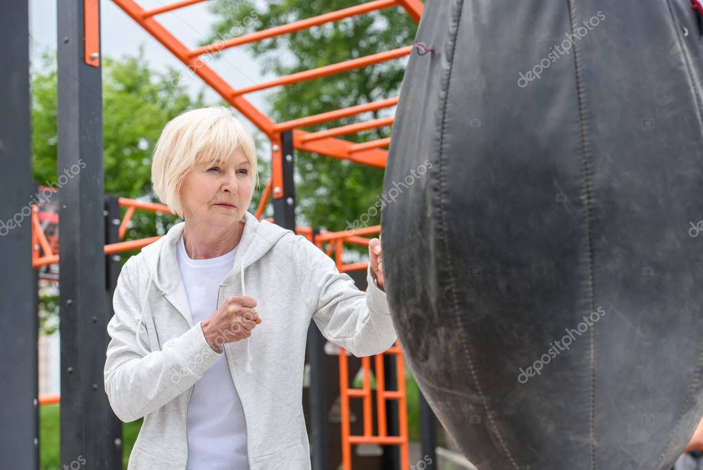 senior woman training with punching bag on sports ground