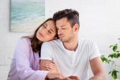 Fotografie sinnliche junge Brautpaar im Schlafanzug zu Hause zusammen sitzen
