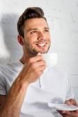pohledný usměvavý mladý muž popíjel kávu ráno doma