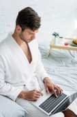 Fotografie young man in bathrobe sitting on bed and using laptop