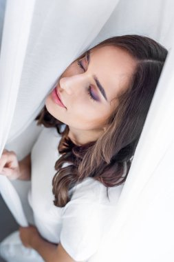 high angle view of beautiful sensual young woman with closed eyes standing behind curtain