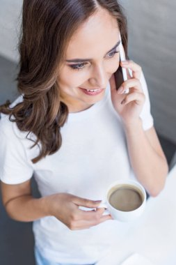 high angle view of beautiful smiling girl holding cup of coffee and talking by smartphone
