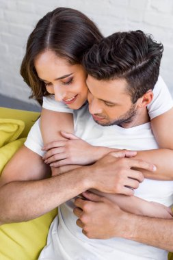 high angle view of beautiful happy young couple hugging at home