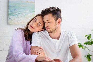 happy sensual young couple in pajamas sitting together at home