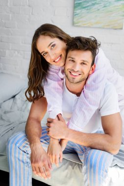 happy young couple in pajamas hugging and smiling at camera