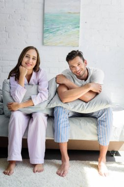 young smiling couple in pajamas sitting on bed with pillows