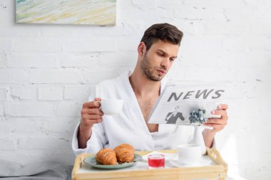 Handsome man in bathrobe reading newspaper during breakfast with coffee stock vector