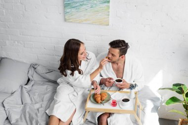 beautiful young couple in bathrobes having breakfast in bed together