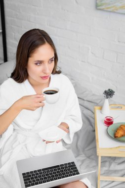 Beautiful woman in white bathrobe with laptop drinking coffee for breakfast stock vector