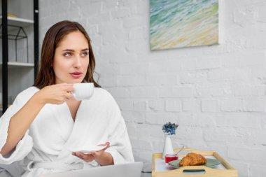 Beautiful woman in white bathrobe drinking coffee for breakfast in bedroom stock vector