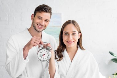 smiling couple in white bathrobes holding alarm clock and standing in bedroom in morning
