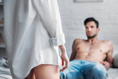 cropped image of girlfriend standing in shirt in front of boyfriend lying on bed in morning
