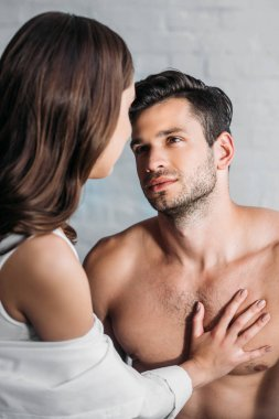 girlfriend touching handsome boyfriends chest at home in morning