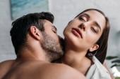 Fotografie boyfriend kissing sensual girlfriends neck in bedroom in morning