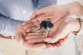 partial view of couple holding keys from new home together